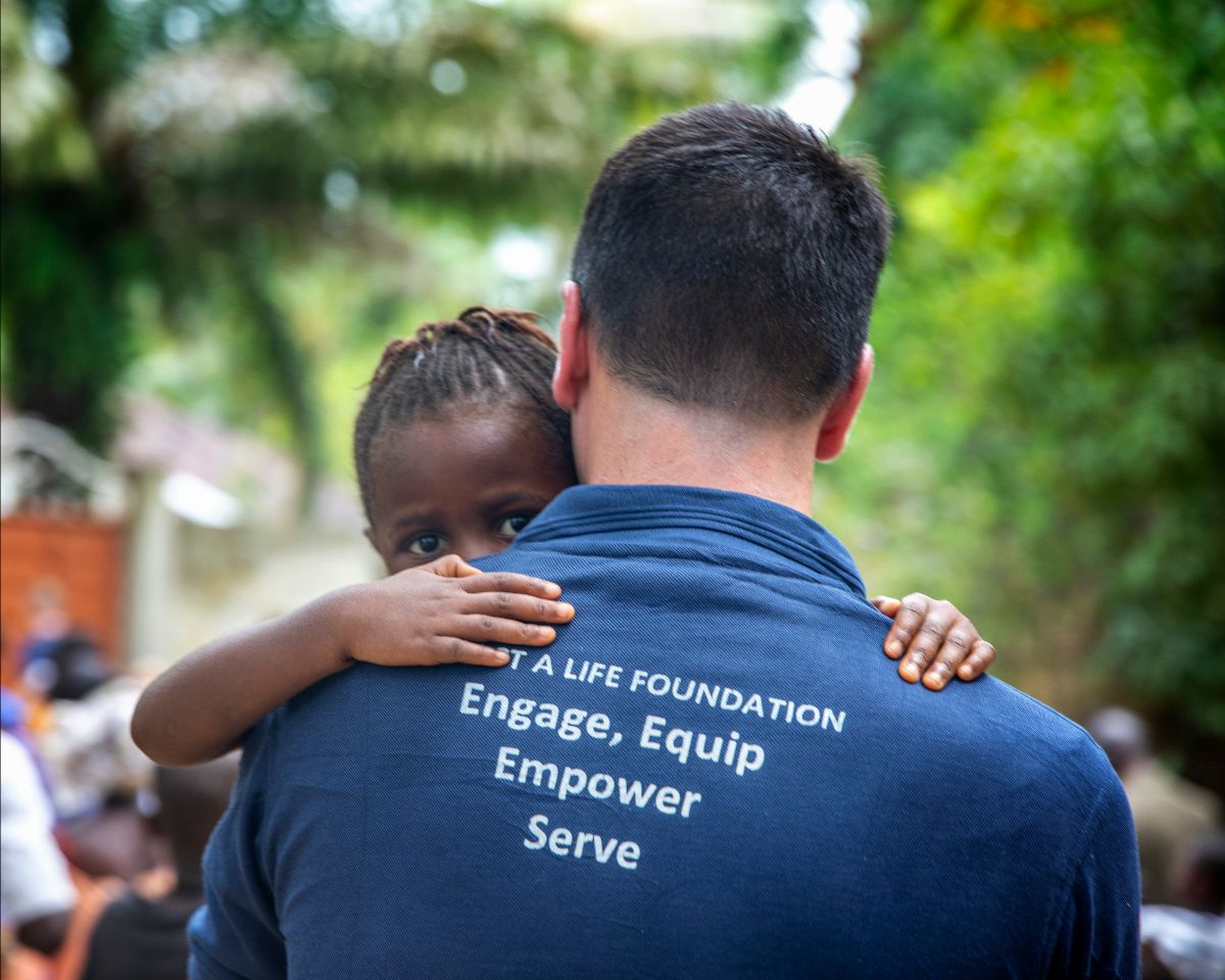 "Volunteer with shirt saying, ""Impact A Life Foundation: Engage, Equip, Empower, Serve"